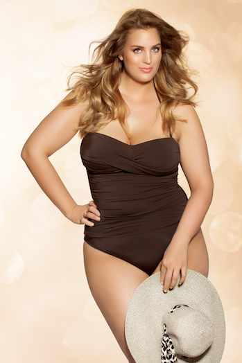 Beautiful plus size model wearing swimsuit and holding summer hat.
